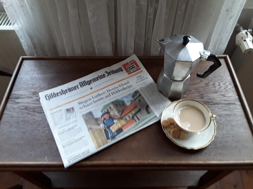 Stillleben: Eine Hildesheimer Zeitung, eine Tasse Kaffee, eine Kanne und einige Kekse