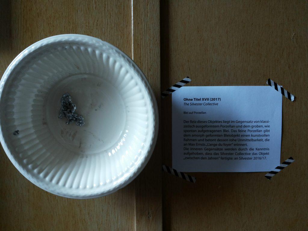 """An der Wand hängt eine kleine Porzellanschüssel mit einem Batzen Blei darin. Daneben eine Objektbeschreibung: Ohne Titel XVII (2017) - The Silvester Collective. Blei auf Porzellan. Der Reiz dieses Objektes liegt im Gegensatz von klassizistisch ausgeformten Porzellan und dem groben, wie spontan aufgetragenen Blei. Das feine Porzellan gibt dem amorph geformten Bleiobjekt einen kunstvollen Rahmen und betont dessen rohe Unmittelbarkeit, die an Max Ernsts """"L'ange du foyer"""" erinnert. Die inneren Gegensätze werden durch die Kenntnis aufgehoben, dass das Silvester Collective das Objekt """"zwischen den Jahren"""" fertigte: an Silvester 2016/17."""