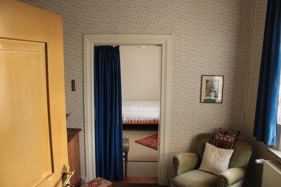 Ansicht von Kerstins Zimmer zu Anfang, als wir das Haus zum ersten Mal besichtigt haben. An den Wänden befindet sich eine Blümchentapete, es ist unter Anderem ein Sessel und ein Bett zu sehen.