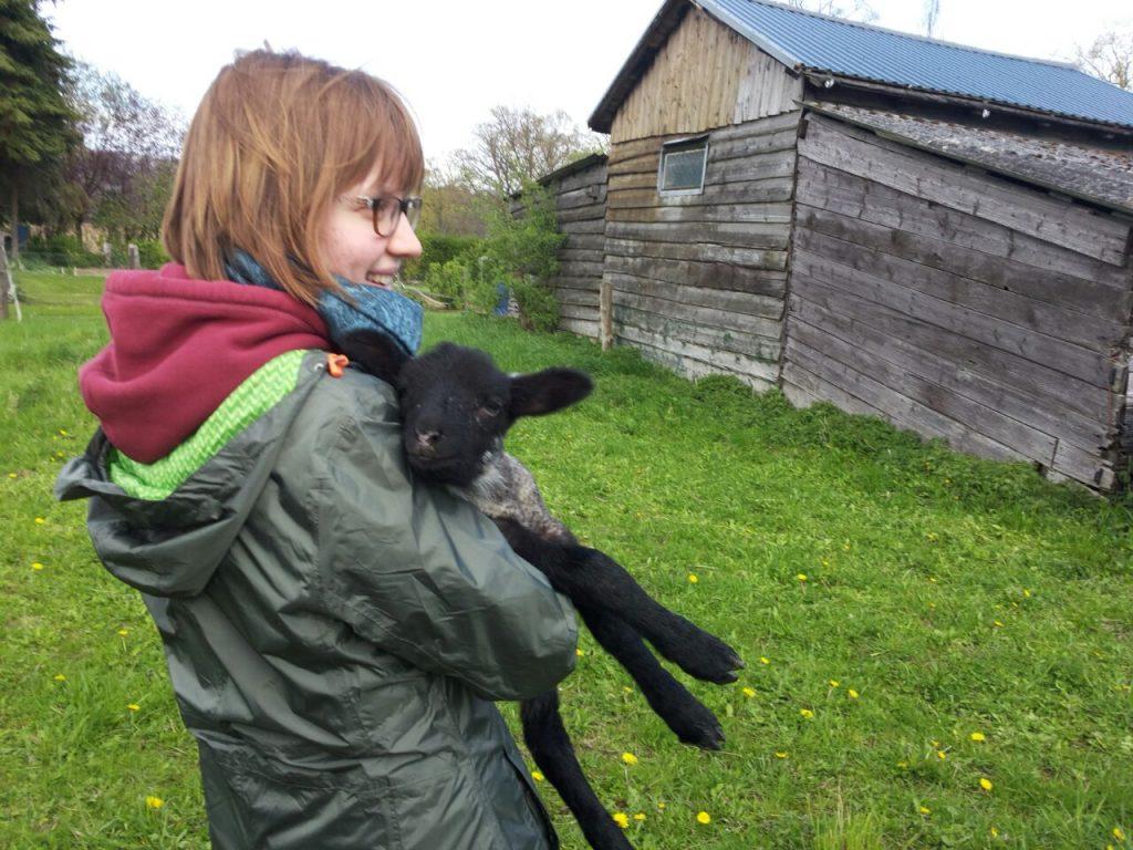 Auf einer grünen Wiese steht Astrid (vom fachwerkhuhn) und hält ein Lamm auf den Armen und strahlt dabei.