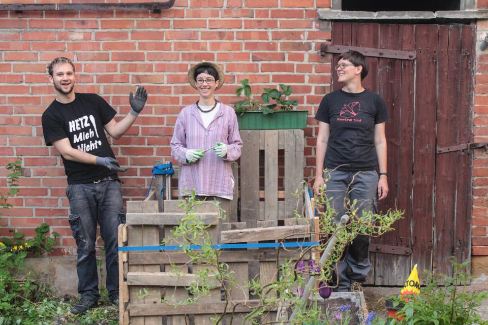 Die Kompostkiste ist fertig und in der Mitte des Bildes zu sehen. In der Kiste steht unsere Freundin, rechts daneben Kerstin und links Bennet. Alle 3 sind froh, dass sie es endlich fertig bekommen haben.