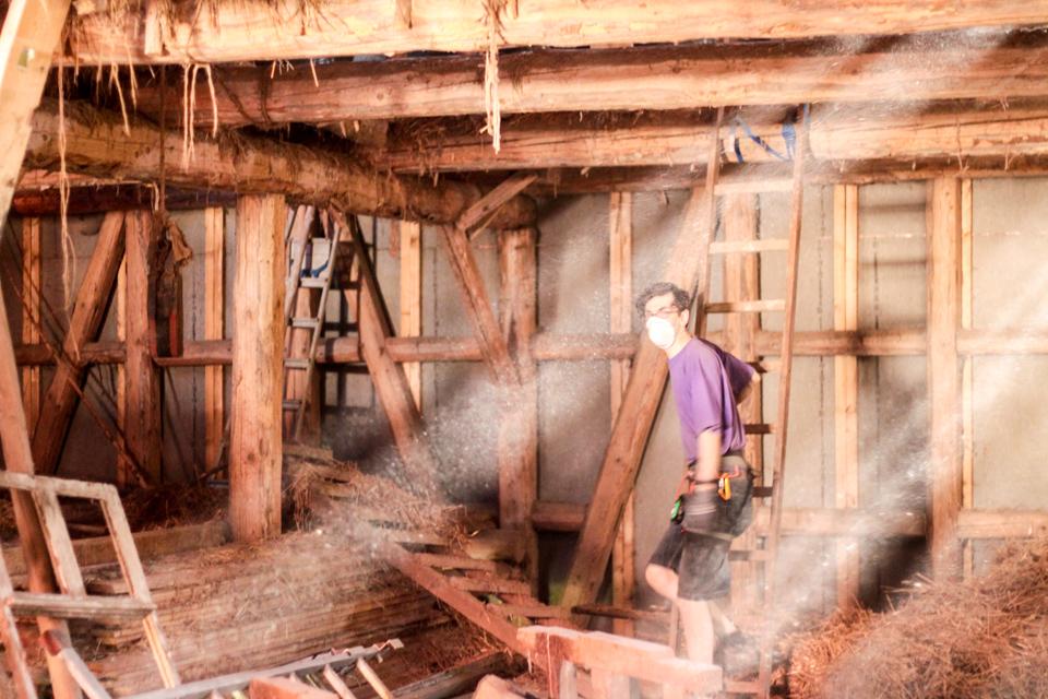 In der Scheune, die voll mit altem Holzund Heu ist, steht Lukas in Arbeitskleidung. Lichtstrahlen kommen durch das Dach.