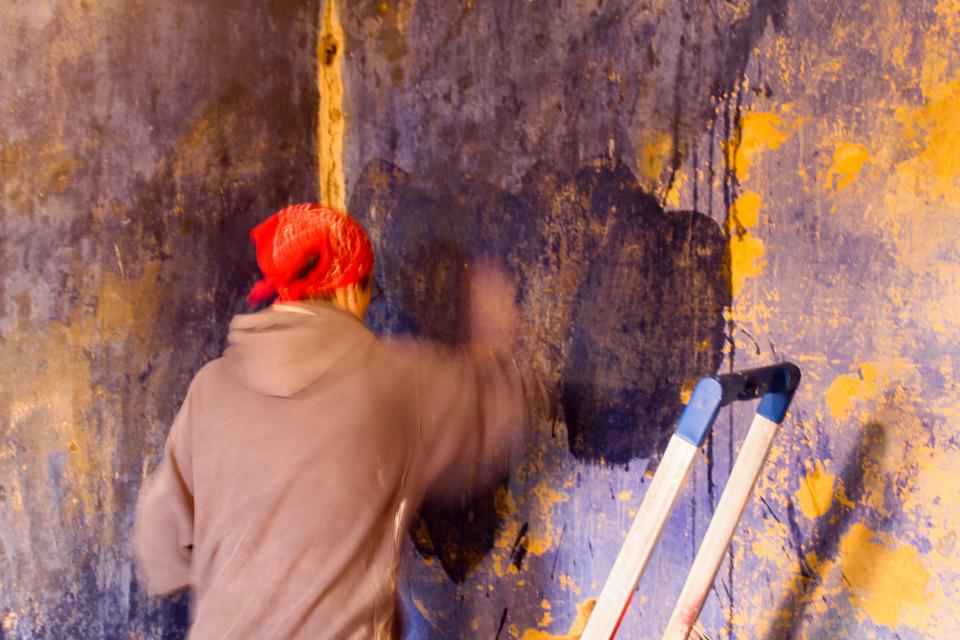 Beim Reinigen der blauen Zimmerwände