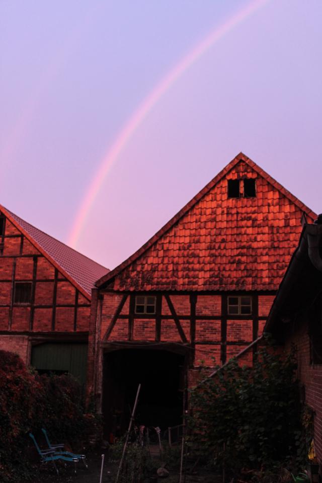 Über dem Dach unserer Scheune ist ein wunderschöner Regebogen am blauen Himmel zu sehen.