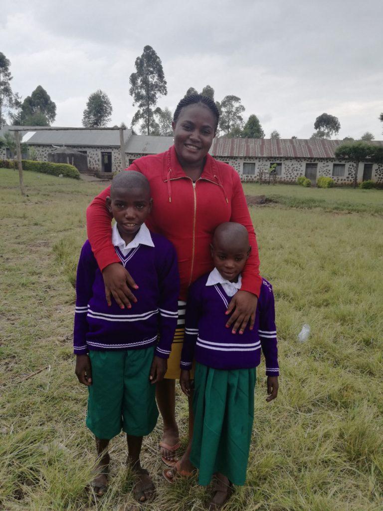 Gertrude (in rotem Pulli) mit zwei Kinden, die ihre Schuluniform tragen
