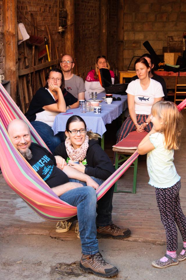 Zuhörer sitzen an einem Biertisch und in einer Hängematte.
