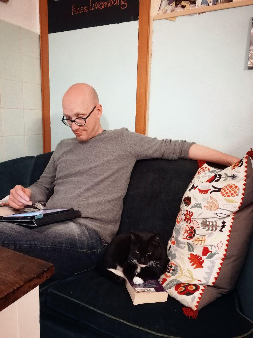 Jan sitzt mit dem Tablet auf dem Sofa und die Katze daneben.