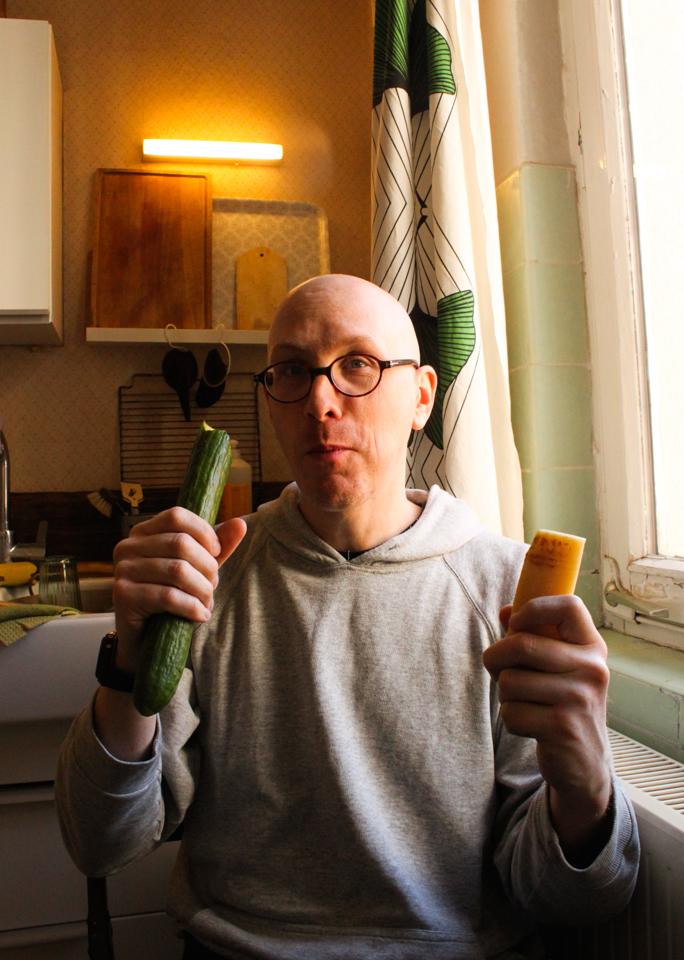 Jan sitzt in der Küche und beißt in eine Gurke. In der anderen Hand hält er ein Stück Parmesan.