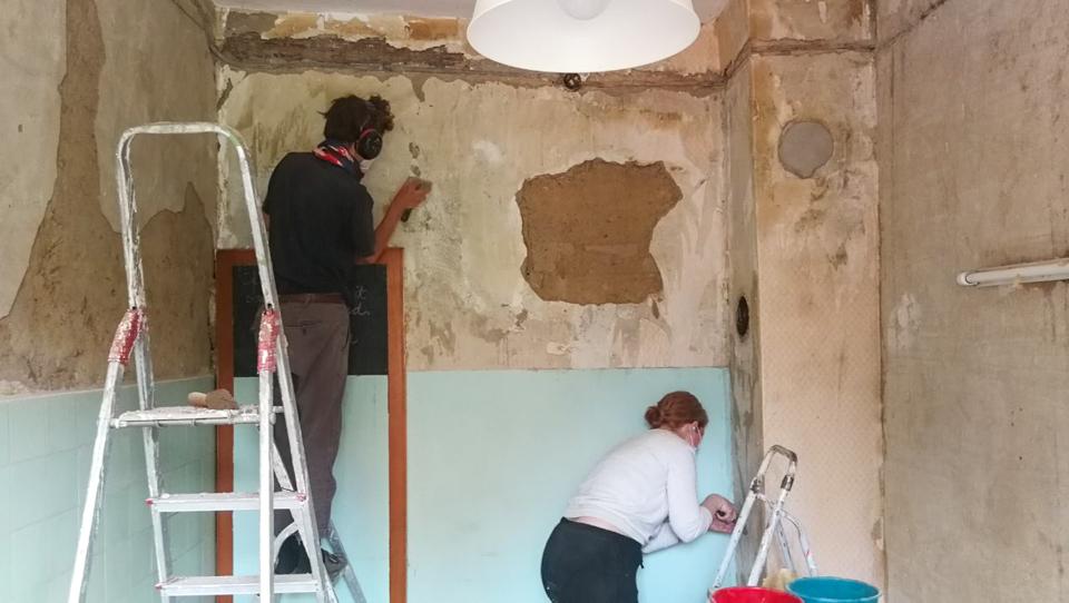 Toni und Gini kratzen Tapete ab von einer sehr marode aussehenden Wand.
